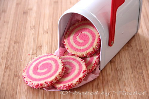 Pink and white spiral patterned sugar cookies coming out of a white mailbox.
