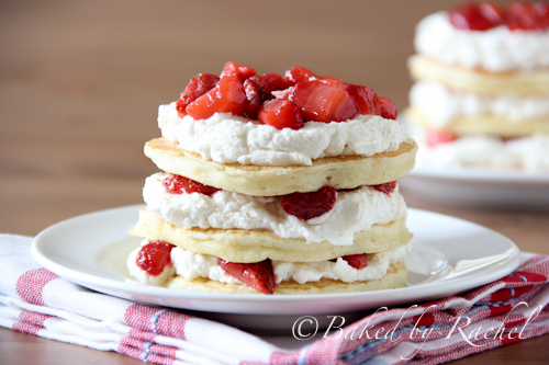 Front view of three pancakes layered with whipped cream and strawberries on small white plate.