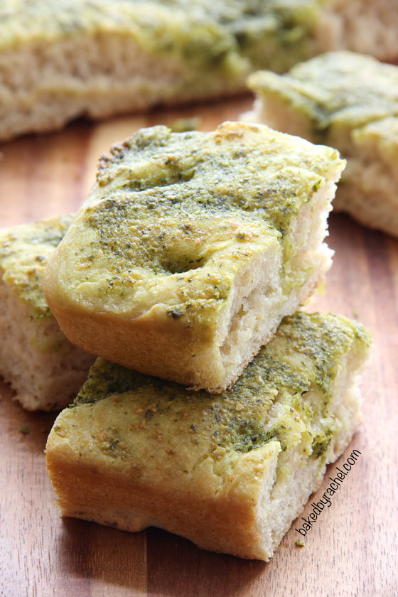 Homemade focaccia bread topped off with a flavorful basil-pesto sauce. Recipe from @bakedbyrachel