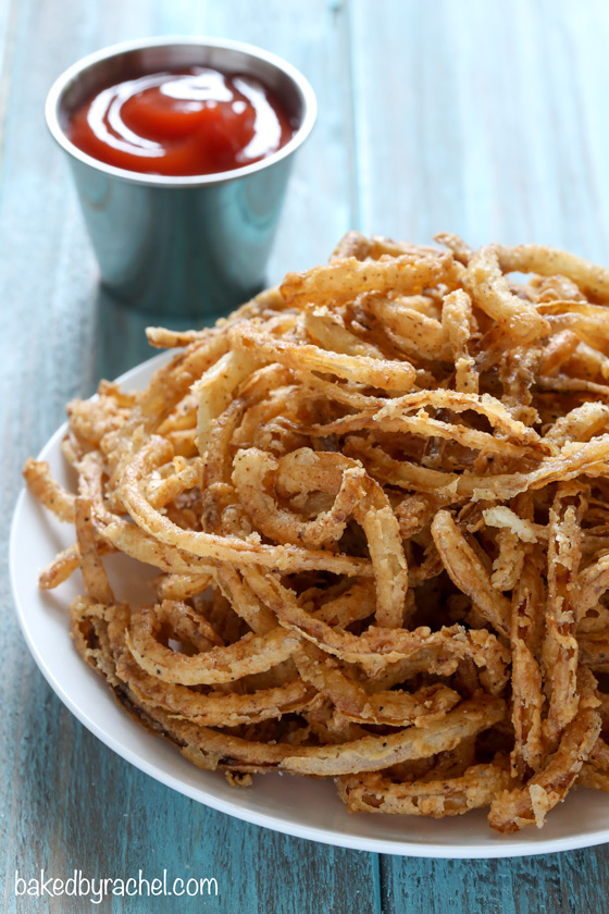 Easy homemade crispy fried seasoned onion strings recipe from @bakedbyrachel. A perfect topping for salads, burgers and more!