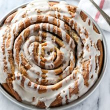Giant fluffy homemade cinnamon roll cake with a sweet vanilla glaze. Recipe from @bakedbyrachel