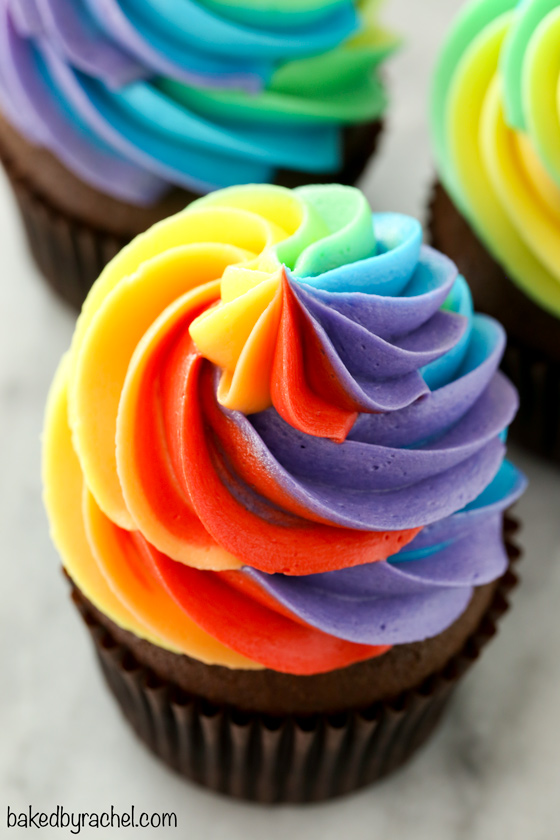 Moist homemade chocolate cupcakes with fluffy rainbow buttercream frosting recipe from @bakedbyrachel A fun and festive treat for St. Patrick's Day celebrations or any day of the year!