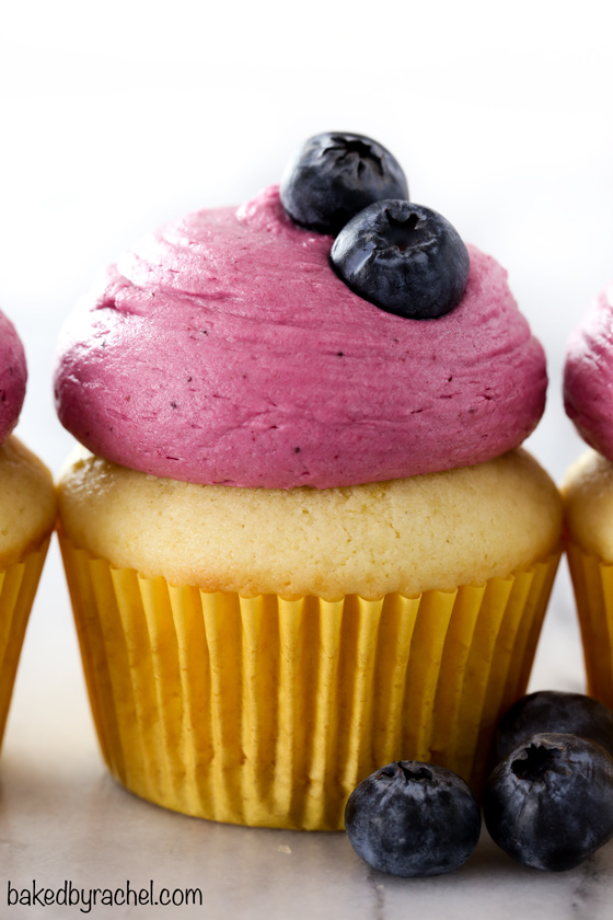 Moist and fluffy homemade lemon cupcakes with fresh lemon curd filling and blueberry buttercream frosting recipe from @bakedbyrachel A fun treat for any spring or summer occasion!