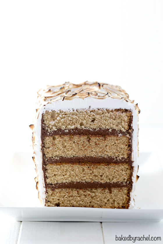 Front image of sliced s'more cake. Layers of cinnamon graham cake with chocolate buttercream filling and coated in toasted marshmallow frosting