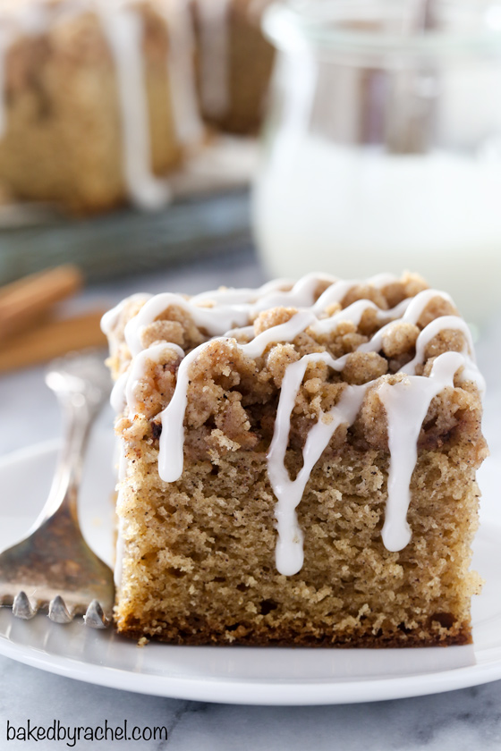 Slice of apple coffee cake with icing drizzle on a white plate